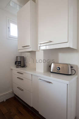 Kitchen equipped with washing machine, refrigerator, crockery, stool