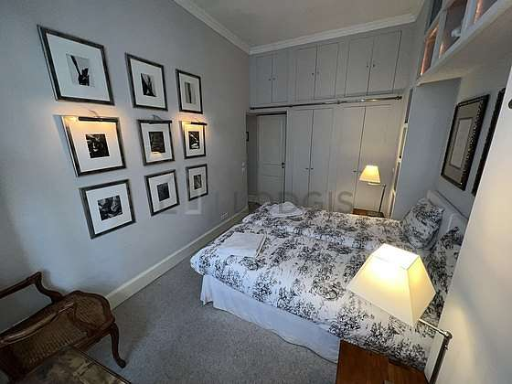 Bright bedroom equipped with desk, wardrobe, cupboard, bedside table