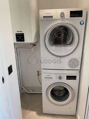 Laundry room with woodenfloor and equipped with washing machine, dryer