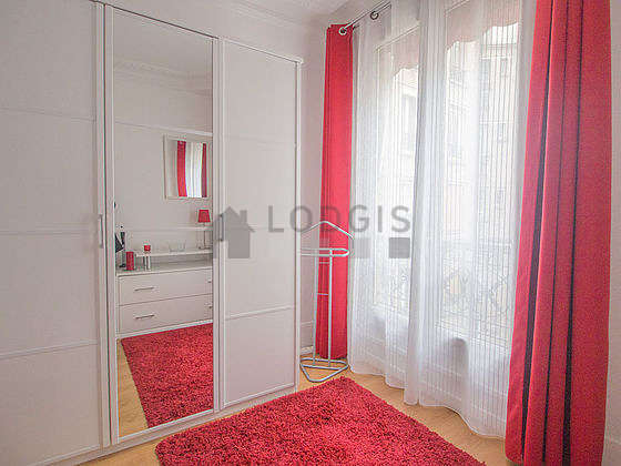 Bright bedroom equipped with closet, storage space, bedside table