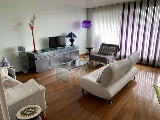 Quiet living room furnished with tv, fan, 1 armchair(s)