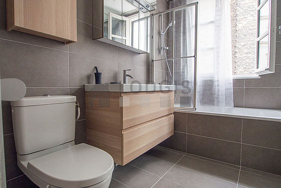 Bathroom equipped with bath tub, towel drying radiator