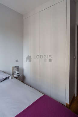 Bright bedroom equipped with air conditioning, tv, 1 armchair(s), bedside table