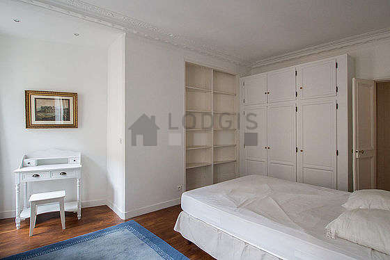 Bright bedroom equipped with tv, stool