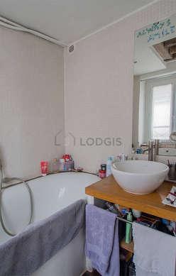 Agréable salle de bain claire avec fenêtres double vitrage et du parquetau sol