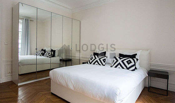 Bright bedroom equipped with wardrobe, cupboard, bedside table