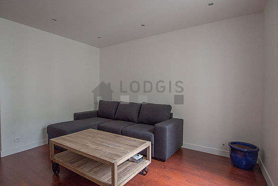 Quiet living room furnished with tv, storage space