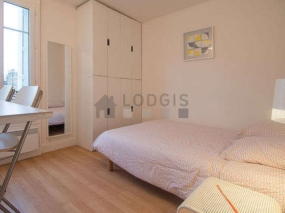 Bright bedroom equipped with air conditioning, tv, stool