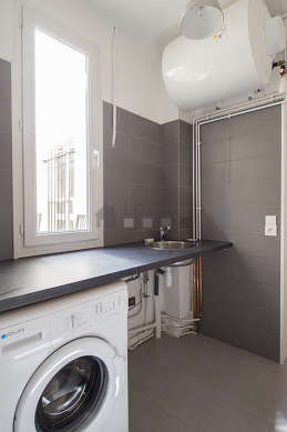 Beautiful laundry room with tilefloor and equipped with washing machine