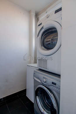 Very beautiful laundry room with tilefloor and equipped with washing machine, dryer, freezer