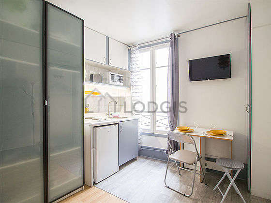 Kitchen equipped with refrigerator, crockery, stool
