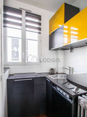 Kitchen equipped with washing machine, kettle, crockery, stool