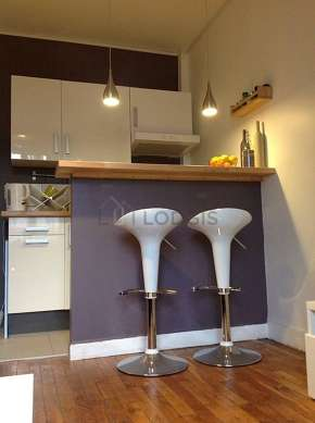 Kitchen equipped with washing machine, refrigerator, extractor hood, stool