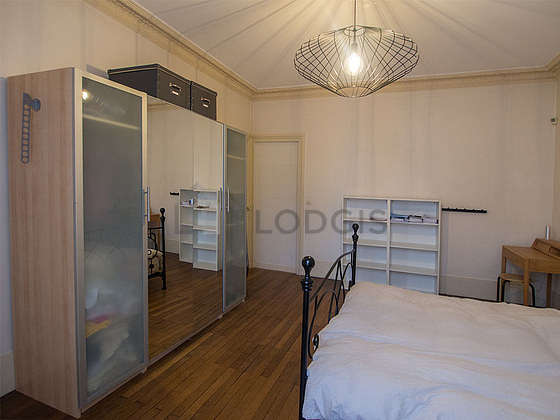 Very bright bedroom equipped with desk, closet, cupboard, bedside table