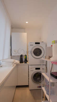 Beautiful laundry room with tilefloor and equipped with washing machine, dryer