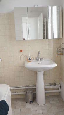 Bathroom equipped with washing machine, bath tub, hair-dryer, electric toilet