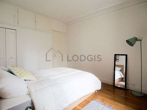 Bright bedroom equipped with cupboard, bedside table