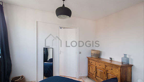 Very bright bedroom equipped with storage space, bedside table