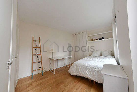Very bright bedroom equipped with desk, wardrobe, cupboard, stool