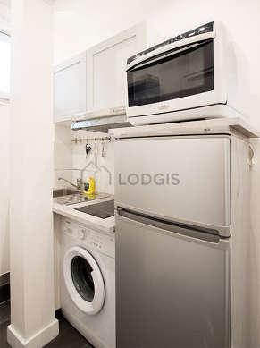 Kitchen equipped with washing machine, crockery, stool