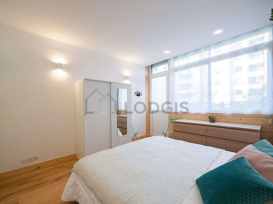Very bright bedroom equipped with closet, storage space, bedside table