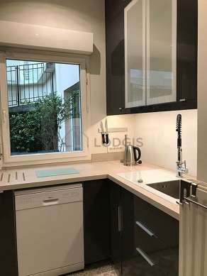 Kitchen equipped with dishwasher, hob, extractor hood, stool