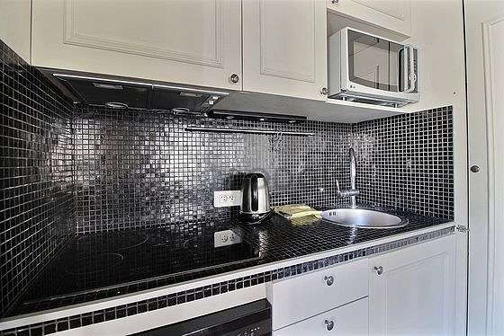 Kitchen equipped with washing machine, refrigerator, extractor hood