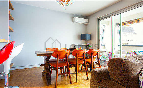 Quiet living room furnished with air conditioning, tv, fan, 1 armchair(s)