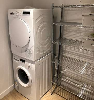 Very beautiful laundry room with woodenfloor and equipped with washing machine, dryer