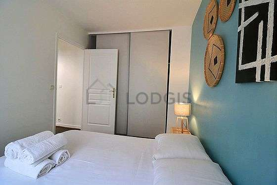 Very bright bedroom equipped with fan, sofa, bedside table