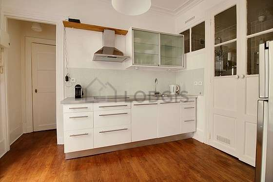 Kitchen equipped with refrigerator, extractor hood