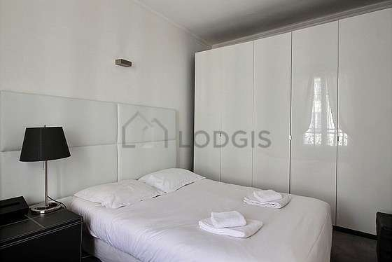 Very bright bedroom equipped with cupboard, bedside table