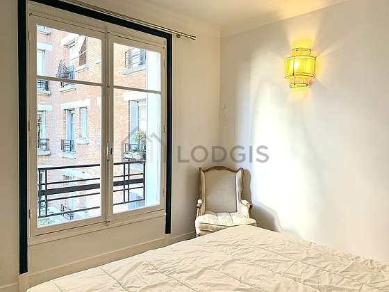 Very bright bedroom equipped with tv, stool
