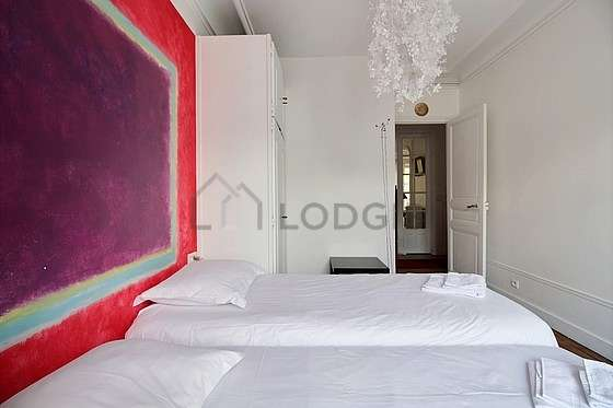 Bright bedroom equipped with cupboard