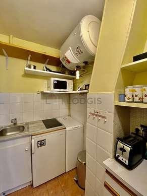 Kitchen equipped with hob, refrigerator, freezer, crockery