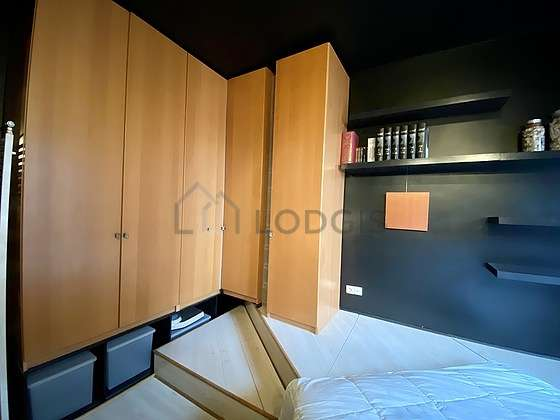 Very bright bedroom equipped with desk, wardrobe, cupboard