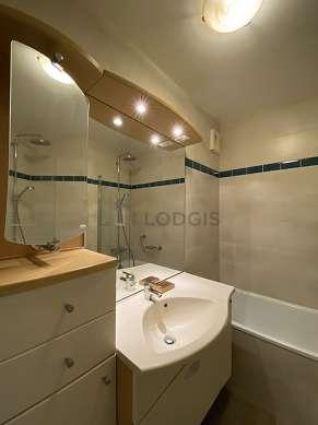Bathroom equipped with washing machine, bath tub, towel drying radiator