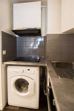Kitchen equipped with washing machine, dryer, kettle, crockery