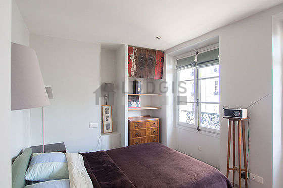 Bright bedroom equipped with storage space, cupboard, bedside table