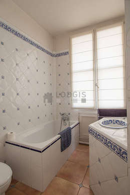 Belle salle de bain claire avec fenêtres et du parquetau sol