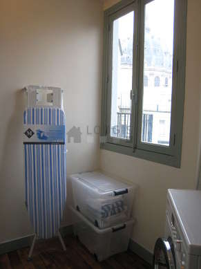 Beautiful laundry room with woodenfloor and equipped with washing machine